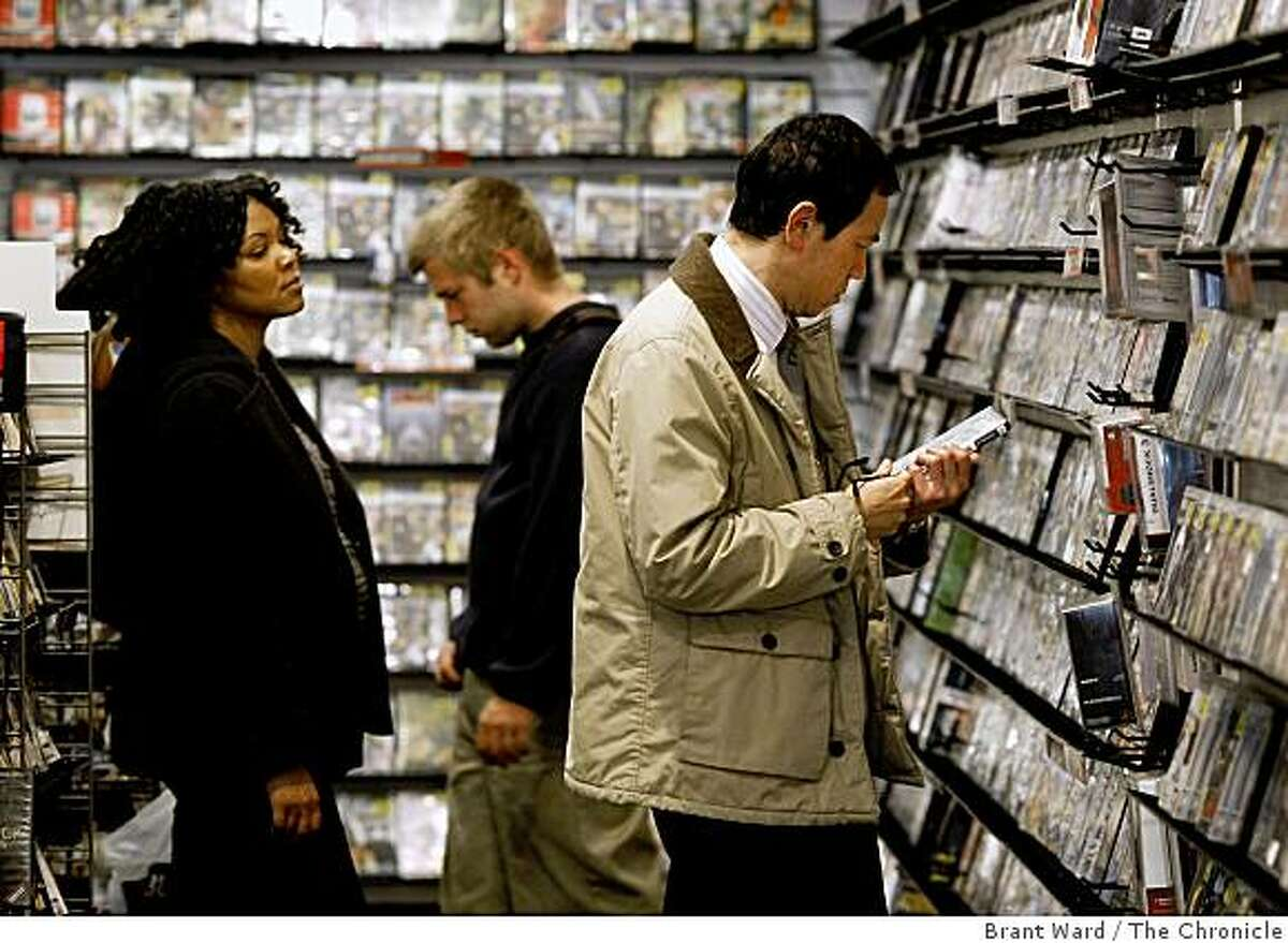 Customers at Gamestop on Powell Street in San Francisco, Calif., looked at both new and used titles on June 2, 2009. Used games, sold at a discount, at retailers like Gamestop are a boon to consumers. Game publishers argue they don't see any profit from the resale of their product.
