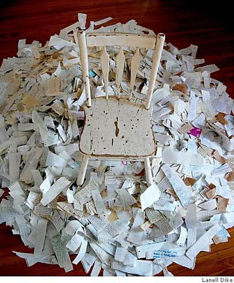 """Artist Lanell Dike says of her photo """"Goodbye,"""" an empty chair and 25 years of torn-up journals: """"The 'I,' the person (individual or collective) who wrote all of the thoughts, documented all of the feelings, everything that happened...walked away. Left the chair, left the past. Walked into the daylight (which can be seen to the right of the photograph, as if coming in through an open door)."""" The work appears at East Bay Open Studios. Photo: Lanell Dike"""
