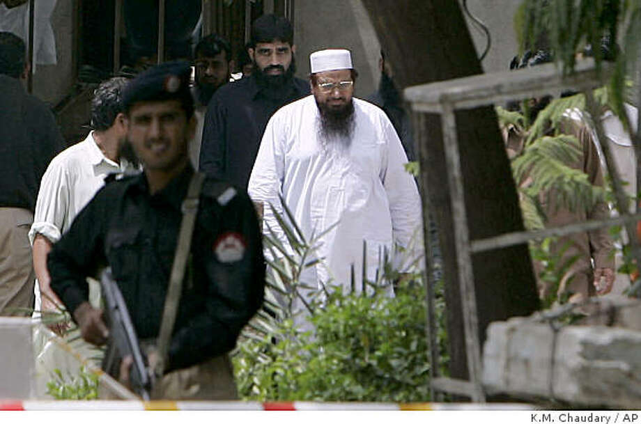 A Pakistani police officer stands guard as Hafiz Mohammed Saeed, center in white dress, chief of an Islamic charity Jamaat-ud-Dawa, walks on the compound of his residence after the Lahore High Court decision regarding his release in Lahore, Pakistan. A Pakistani court on Tuesday ordered the release of the hardline Islamist cleric allegedly linked to the attacks in the Indian city of Mumbai, his lawyer said, setting the stage for a new round of tensions between the two countries. (AP Photo/K.M. Chaudary) Photo: K.M. Chaudary, AP