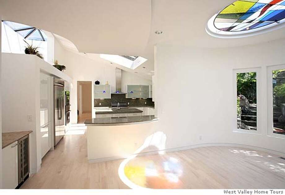 """stained glass skylight in gathering area of Los Gatos house where Steve Wozniak raised his kids. Developer has gutted and redone it, keeping some Woz details such as a backyard cave and """"pet hotel."""" It's on the market for $10 million.  Ran on: 09-03-2006  When Steve Wozniak owned this Los Gatos home it was nondescript. On the outside not much has changed, left. But a gut and rebuild inside has added sinuous curves and lots of light, top right. The cave, built for Woz's kids by experts from the California Academy of Sciences, top left, remains. Photo: West Valley Home Tours"""