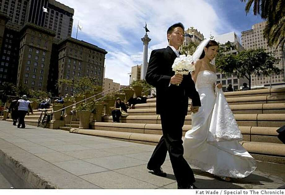 Wedding Season has begun as newlyweds, Duc and Maggie Ha stroll past Union Square on their way to a photo shoot at Union Square in San Francisco, Calif. on Monday, June 1, 2009. Photo: Kat Wade, Special To The Chronicle