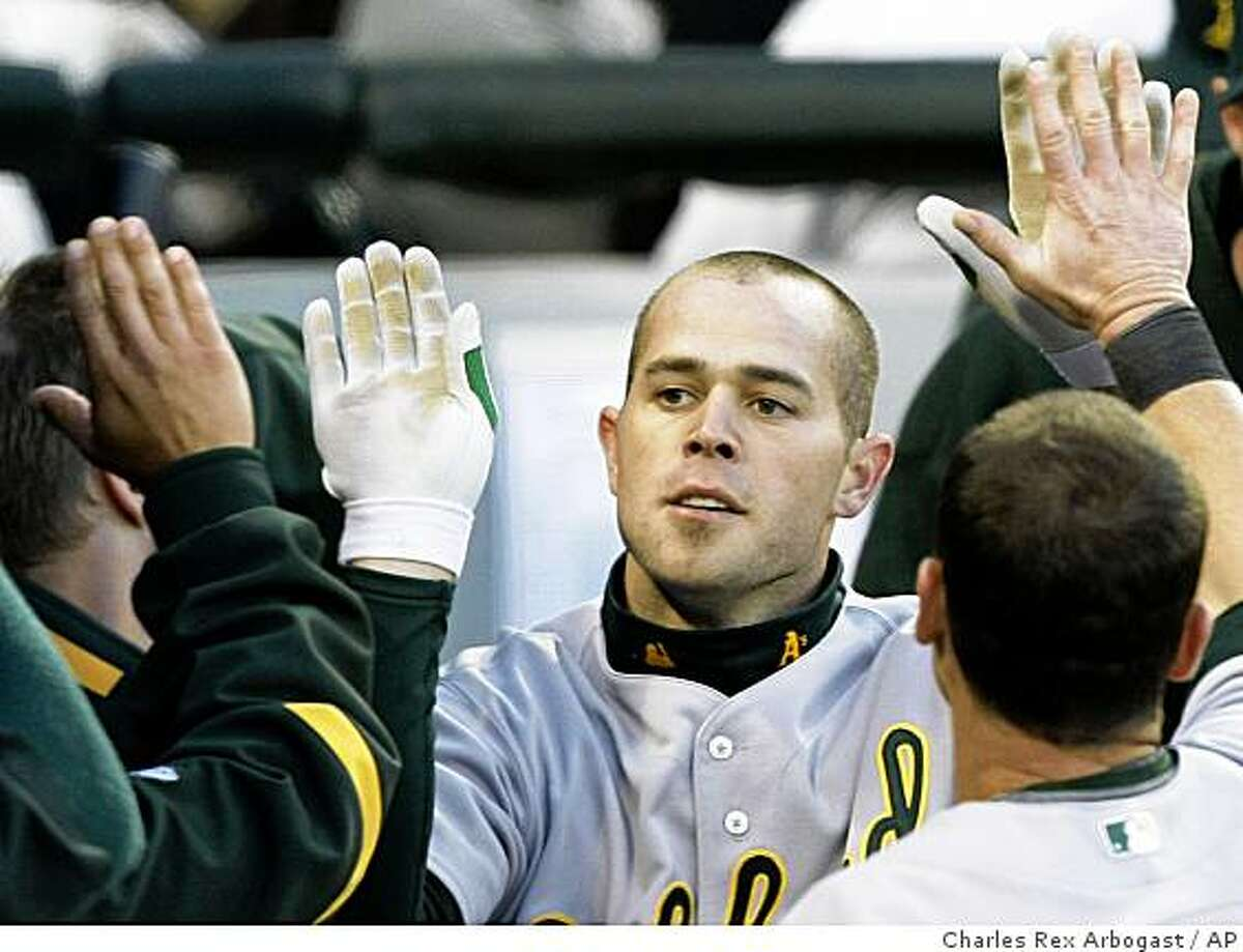Oakland Athletics' Bobby Crosby is greeted in the dugout after hitting a home run off Chicago White Sox starting pitcher Clayton Richard during the fourth inning of a baseball game Wednesday, June 3, 2009, in Chicago.
