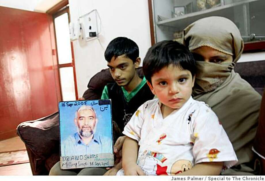 Zahida Sharif , 42, holds her 3-year-old son Hufzia while her oldest son Hamza, 14, displays a photo of his fahter Abid Sharif in the family's home in Rawalpindi, Pakistan.  Abid Sharif, a suspected victim of enforced disappearance, was 50 at the time he went missing during a visit to the northwest city of Peshawar on Sept. 16, 2005 ? one month before Huzfia was born.Enforced disappearances in Pakistan were extremely rare before the Sept. 11 attacks catalyzed the so-called worldwide war on terror by the United States and its allies, according to the human rights group Amnesty International.  The Defense of Human Rights  have registered 565 possible cases of enforced disappearance, but the group estimates that up to 10,000 people may have disappeared under Musaharraf's reign.JAMES PALMER / FOR THE CHRONICLE Photo: James Palmer, Special To The Chronicle