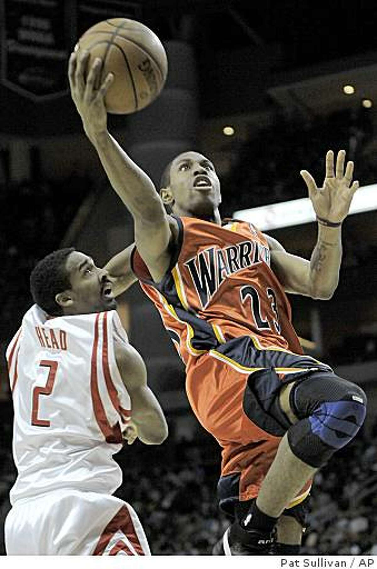 Golden State Warriors' C.J. Watson (23) goes for two points over Houston Rockets defender Luther Head (2) during the first half of a basketball game Tuesday, Jan. 29, 2008 in Houston. (AP Photo/Pat Sullivan)