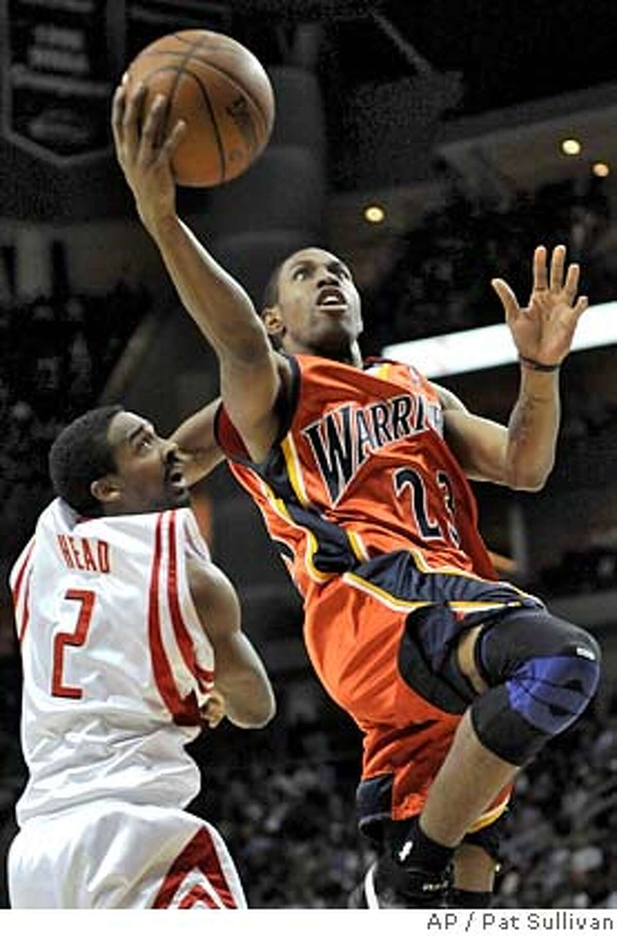 Golden State Warriors' C.J. Watson (23) goes for two points over Houston Rockets defender Luther Head (2) during the first half of a basketball game Tuesday, Jan. 29, 2008 in Houston. (AP Photo/Pat Sullivan) EFE OUT