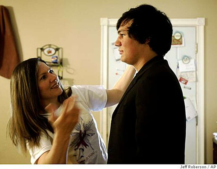 Brryan Jackson stands still as his mother Jennifer Jackson fixes his hair at their home Thursday, June 4, 2009, in St. Charles, Mo. As a baby, Brryan's father secretly injected him with a syringe of HIV-tainted blood in hopes of killing the child, but on Saturday, the now-18-year-old will graduate high school, and is stepping up his public speaking about fighting the stigma of AIDS and the power of faith and forgiveness. (AP Photo/Jeff Roberson) Photo: Jeff Roberson, AP