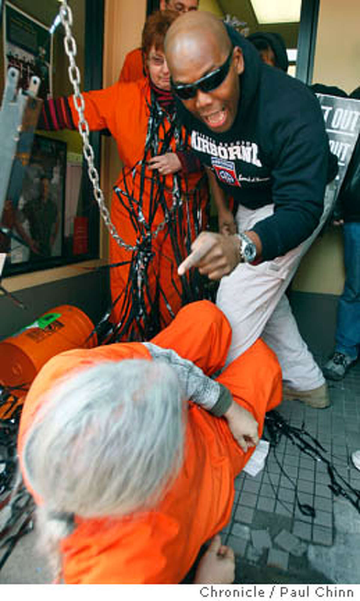 An unidentified man, top, yells at anti-war protester Don Spark and other activists that chained themselves together in an attempt to block the entrance to a Marine Corps. recruitment office in Berkeley, Calif. on Friday, Feb. 1, 2008. Several scuffles ensued when people attempted to enter the office.