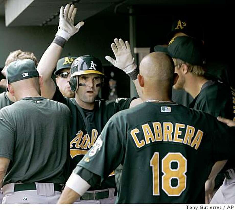 Oakland Athletics' Adam Kennedy is congratulated by teammates following his home run off Texas Rangers' Frank Francisco in the ninth inning of a baseball game in Arlington, Texas, Sunday, May 31, 2009. Oakland won 5-4. (AP Photo/Tony Gutierrez) Photo: Tony Gutierrez, AP
