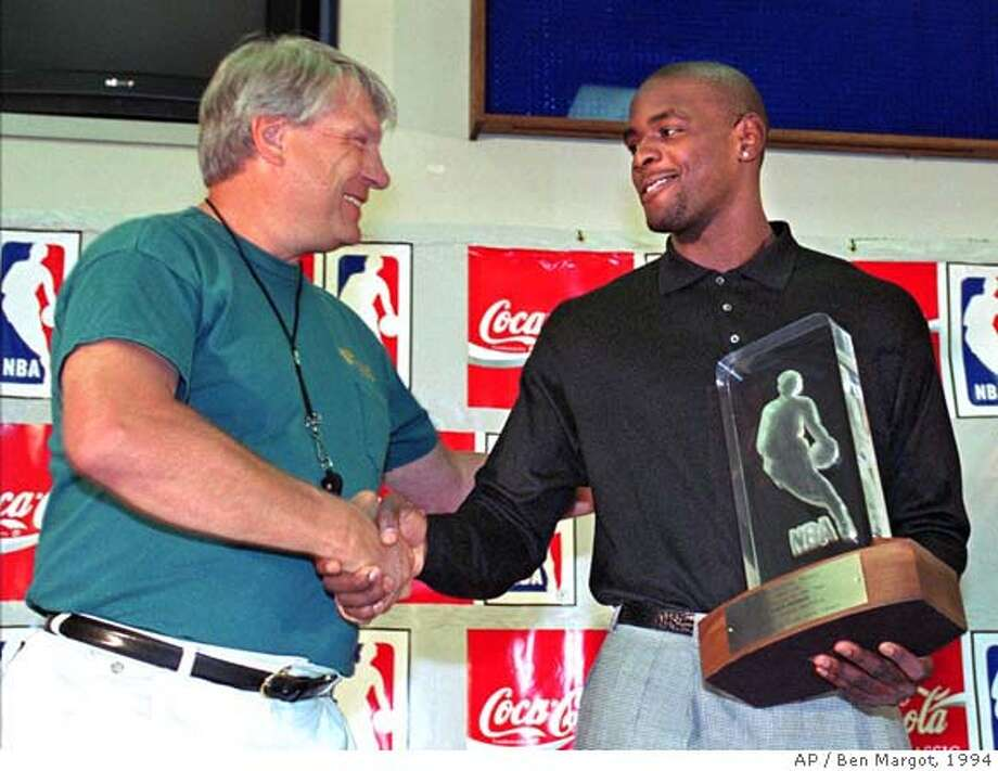 Golden State Warriors' Chris Webber, right, receives a handshake from Warriors head coach Don Nelson during a news conference Tuesday, May 3, 1994, at the Oakland, Calif., Coliseum Arena, where Webber was named the 1994 NBA Rookie of the Year. At 21 years of age, Webber is the second-youngest player in history to receive the award; Shaquille O'Neal was two days younger when he received the Gottlieb trophy. (AP Photo/Ben Margot) ALSO RAN: 2/11/2000 CAT Photo: BEN MARGOT