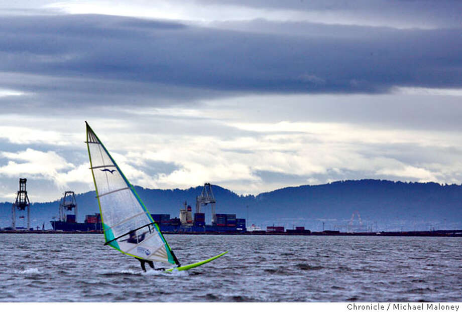 A sail boarder takes advantage of the brisk winds off of the Berkeley Marina Sunday morning, January 27, 2008. The ever changing storm clouds over the Port of Oakland provided a scenic backdrop. Photo by Michael Maloney / The Chronicle Photo: Michael Maloney