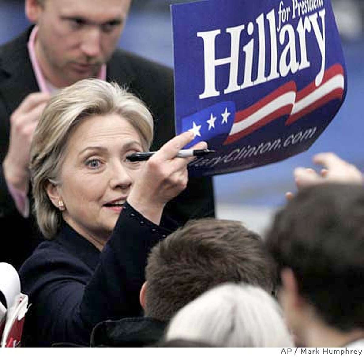 Democratic presidential hopeful Sen. Hillary Rodham Clinton, D-N.Y., reaches for a campaign poster to sign at Tennessee State University in Nashville, Tenn., Saturday, Jan. 26, 2008.(AP Photo/Mark Humphrey)