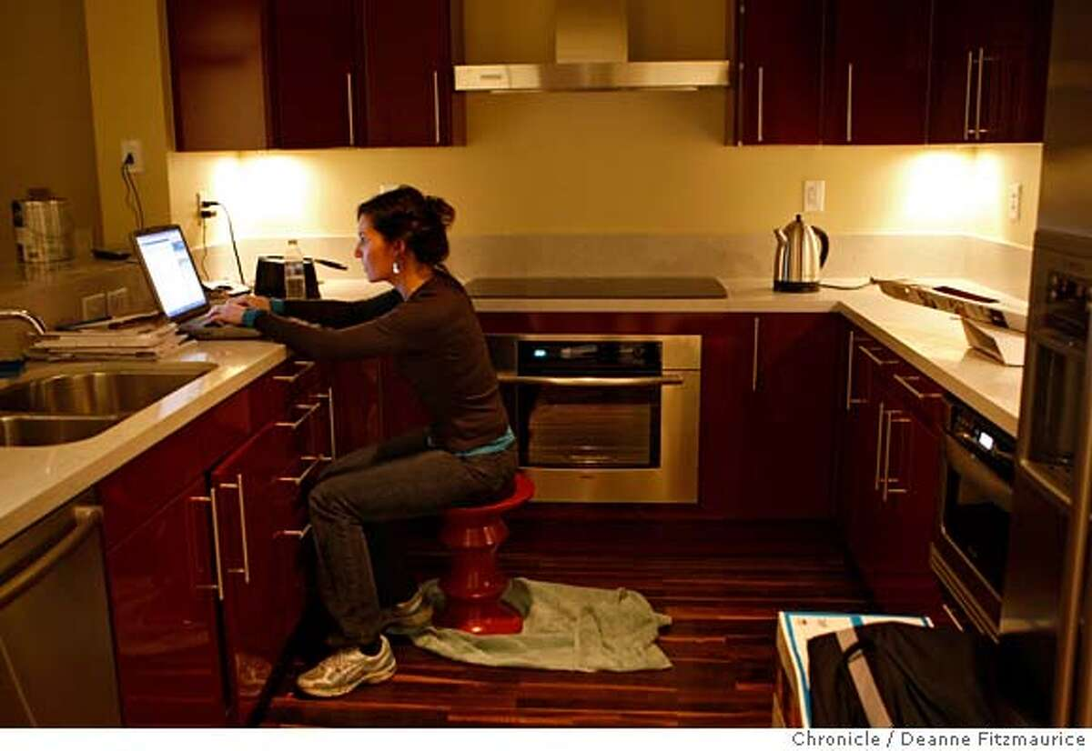 .jpg Denise McCullough works at her kitchen counter since she does not have furniture yet. She is buying items for her new home on her laptop in the kitchen of the condo she is just moving into. She and her husband, a couple from Victoria, Canada bought a condo in San Francisco as it became affordable since the drop in value of the US Dollar. Photographed in San Francisco on 1/11/08. Deanne Fitzmaurice / The Chronicle Mandatory credit for photographer and San Francisco Chronicle. No Sales/Magazines out.