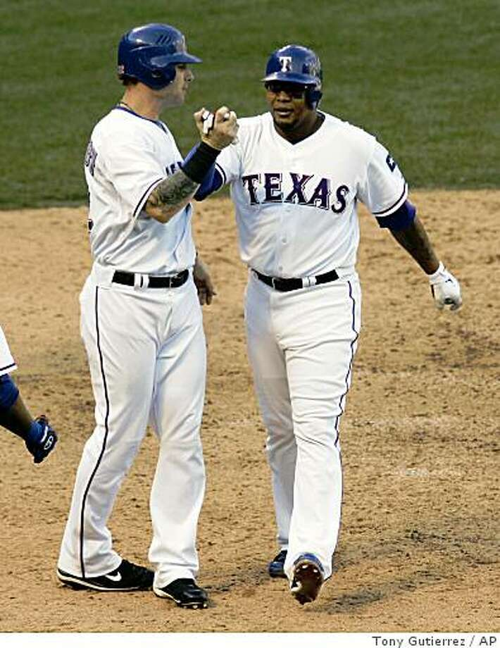 Texas Rangers' Josh Hamilton, left, greets teammate Andruw Jones, right, at home following his two-run home run off Oakland Athletics' Santiago Casilla that also scored Hamilton in the eighth inning of a baseball game in Arlington, Texas, Friday, May 29, 2009. The Rangers won 6-3. (AP Photo/Tony Gutierrez) Photo: Tony Gutierrez, AP