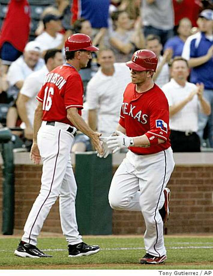 Baseball fans cheer as Texas Rangers third base coach Dave Anderson (16) congratulates Hank Blalock on his solo home run off of Oakland Athletics' Brett Anderson in the fourth inning of a baseball game in Arlington, Texas Saturday, May 30, 2009. The Rangers won 14-1.(AP Photo/Tony Gutierrez) Photo: Tony Gutierrez, AP