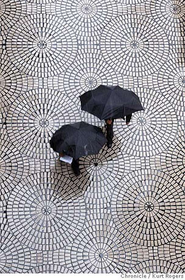 This couple walks down Front st near the Embarcadero Center in the rain. Rain heavy at times in San Francisco.  Kurt Rogers / The Chronicle Photo: Kurt Rogers