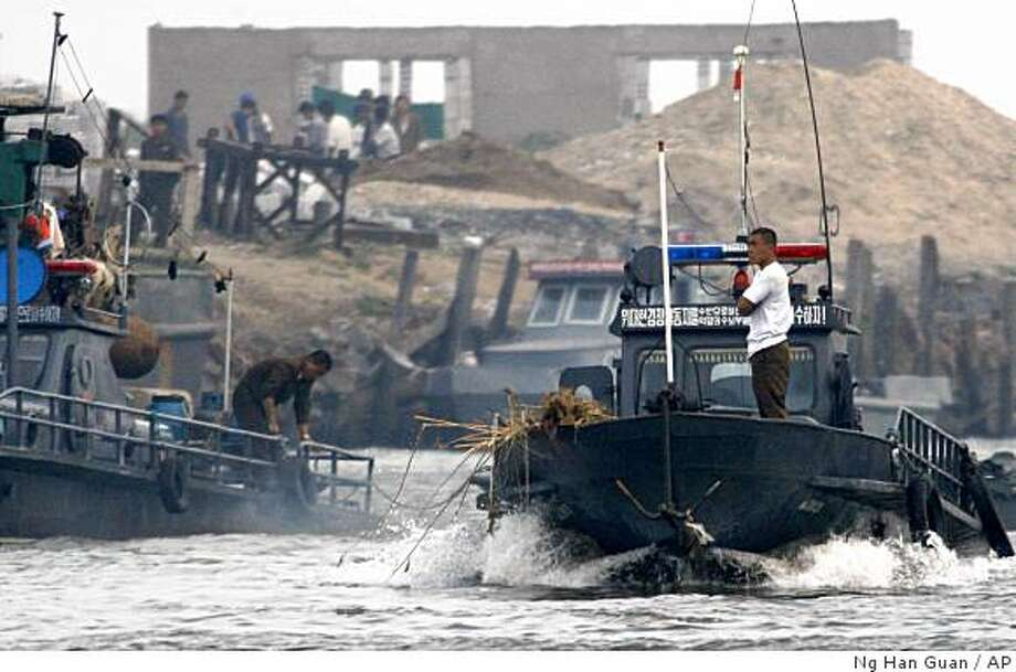 A North Korean patrol boat inspects activity along the North Korean Sinuiju river bank, seen along the Yalu river near Dandong, northeastern China's Liaoning province, Monday, June 1, 2009. North Korea has transported its most advanced missile, believed to be capable of reaching Alaska, to a launch site on its west coast near China, news reports said Monday. (AP Photo/Ng Han Guan) Photo: Ng Han Guan, AP