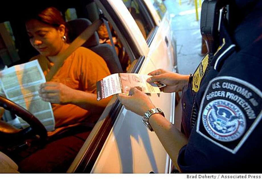 A U.S. Customs and Border Protection officer hands documents to a woman entering the U.S. from Mexico, at the Brownsville, Texas border crossing Monday, June 1, 2009. The vehicle line for people entering the U.S. from Mexico at the Gateway International Bridge in Brownsville,Texas was short Monday morning, the first day of stricter identification requirements for Americans re-entering the country from Mexico or Canada. Photo: Brad Doherty, Associated Press