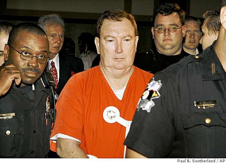 Jerome Ersland is escorted out of a courtroom by Oklahoma County sheriff deputies after a bond hearing at the Oklahoma County Courthouse in Oklahoma City Thursday, May 28, 2009. Confronted by two holdup men, pharmacist Jerome Ersland pulled a gun, shot one of them in the head and chased the other away. Then, in a scene recorded by the drugstore's security camera, he went behind the counter, got another gun, and pumped five more bullets into the wounded teenager as he lay on the floor. Now Ersland has been charged with first-degree murder in a case that has stirred a furious debate over vigilante justice and self-defense and turned the pharmacist into something of a folk hero. (AP Photo/The Oklahoman, Paul B. Southerland) Photo: Paul B. Southerland, AP