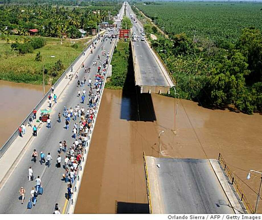 One of the lanes of 'La Democracia' bridge over the Ulua river, built by the French in 1963, had its central section collapsed due to an eartquake May 28, 2009 in El Progreso, 270 km north of Tegucigalpa. A powerful 7.1-magnitude earthquake rocked Honduras on Thursday, killing at least one person whose home collapsed, and sending panicked residents onto the streets. The quake, which shook the country for more than 30 seconds in the middle of the night, injured at least seven people and caused major material damage to homes and infrastructure, officials said. Photo: Orlando Sierra, AFP / Getty Images