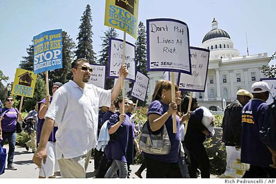 Home health care workers and their supporters march past the Capitol to protest proposed state budget cuts to in-home health care services in Sacramento, Calif. on Wednesday, May 27, 2009. Facing a projected $24.3 billion budget deficit, Gov. Arnold Schwarzenegger and Democratic lawmakers are pressing the Obama Administration for federal loan guarantees to help the state out of a desperate, multi-billion dollar jam. (AP Photo/Rich Pedroncelli) Photo: Rich Pedroncelli, AP
