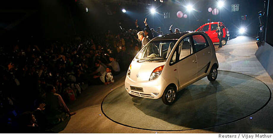 """India's Tata Group Chairman, Ratan Tata (C), poses with the company's new """"Nano"""" car during its launch at the 9th Auto Expo in New Delhi January 10, 2008. The car, a hatchback with a 624cc engine, is priced at about 100,000 rupees ($2,500), half that of the current cheapest car in the market, and is a sharp contrast to the luxury Jaguar and Land Rover brands that Tata is negotiating to buy from Ford Motor Co. REUTERS/Vijay Mathur (INDIA) Photo: VIJAY MATHUR"""