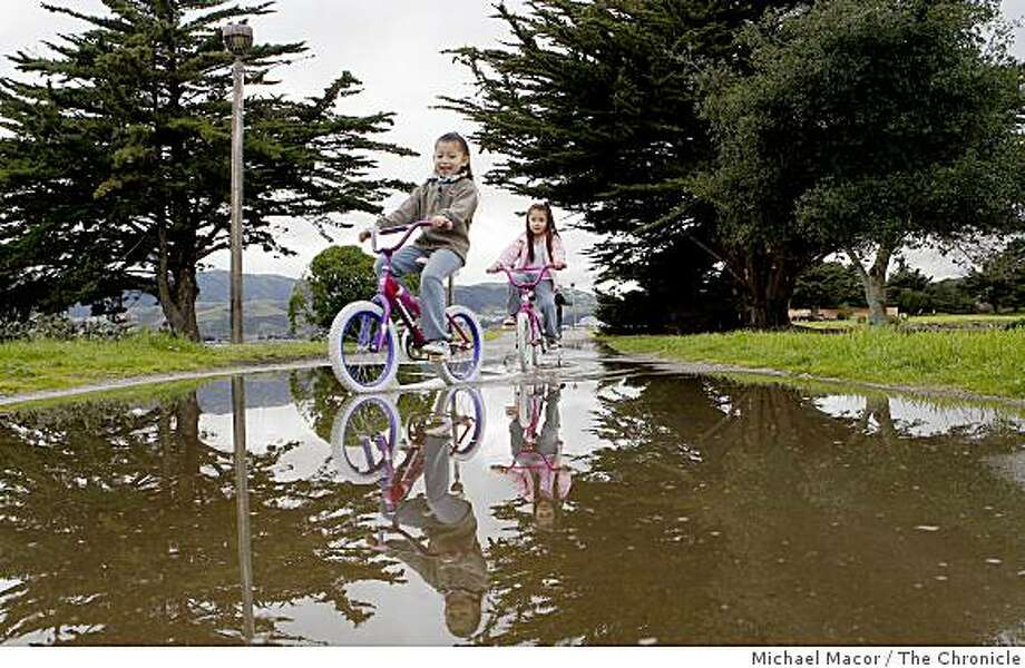 Jessica Lopez,(left) 8-years-old and her sister Cecilia, 6-years-old, ride their bikes through a puddle left behind from this morning's rains at the Candlestick Point recreation area in San Francisco, Calif. on Friday Feb. 6, 2009. More rain is expected to continue through the weekend bringing much needed rain to the Bay Area. Photo: Michael Macor, The Chronicle