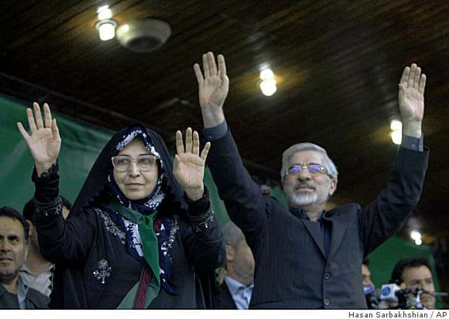 FILE - This May 25m 2009, file photo of leading reformist candidate in the upcoming Iranian presidential elections, Mir Hossein Mousavi, right, gesturing to his supporters, with his wife Zahra Rahnavard, during a campaign rally in Tabriz, Iran, Monday, May 25, 2009. Mousavi, a former prime minister of Iran, is one of the main challengers of the hard-line President Mahmoud Ahmadinejad in the June 12 presidential elections. The political power couple is a common fixture in campaigns in West, but Mousavi and his wife are breaking new ground in Iran in the race for the June 12 presidential election.AP Photo/Hasan Sarbakhshian) Photo: Hasan Sarbakhshian, AP