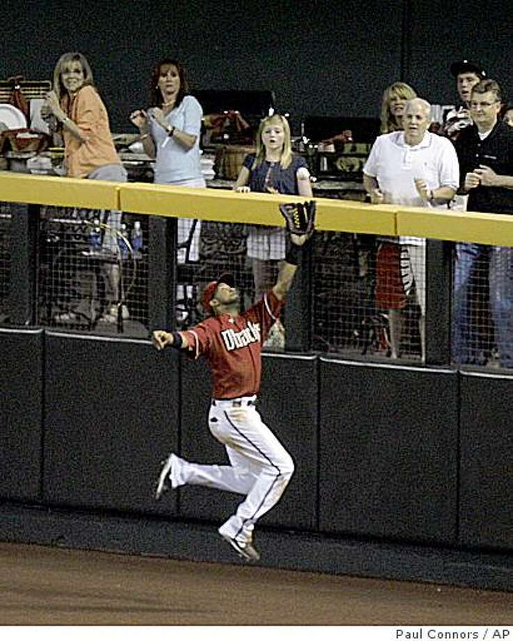 Arizona Diamondbacks centerfielder Chris Young leaps to make the catch on a fly ball hit to the wall by San Diego Padres' Kevin Kouzmanoff for the final out of the game in the ninth inning of a baseball game Tuesday, May 26, 2009, in Phoenix. The Diamondbacks won 6-5. (AP Photo/Paul Connors) Photo: Paul Connors, AP