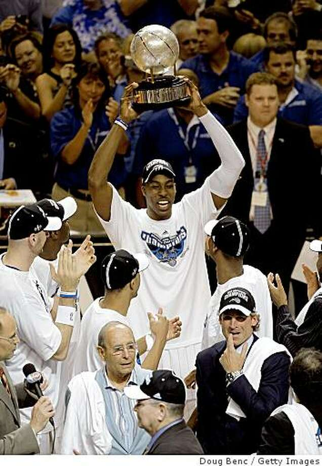 ORLANDO, FL - MAY 30: Dwight Howard #12 of the Orlando Magic holds up the trophy after defeating the Cleveland Cavaliers in Game Six of the Eastern Conference Finals during the 2009 Playoffs at Amway Arena on May 30, 2009 in Orlando, Florida. NOTE TO USER: User expressly acknowledges and agrees that, by downloading and or using this photograph, User is consenting to the terms and conditions of the Getty Images License Agreement  (Photo by Doug Benc/Getty Images) Photo: Doug Benc, Getty Images