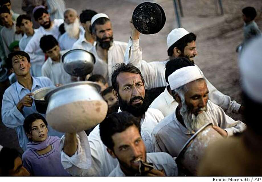 Pakistani displaced people line up as they wait their turn for their ration during a food distribution at Jalozai refugee camp in Peshawar, Pakistan, Monday, May 25, 2009. The Taliban urged civilians Monday to return to the main town in Pakistan's Swat Valley, promising they won't attack security forces battling insurgents there but stopping short of calling the move a cease-fire. (AP Photo/Emilio Morenatti) Photo: Emilio Morenatti, AP