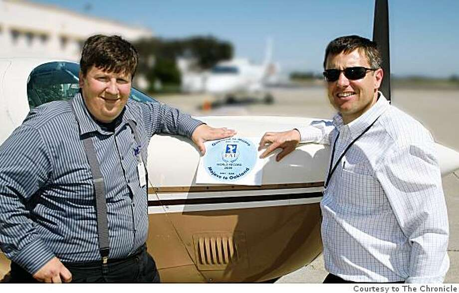Christopher Freeze (left) and Rodrigo von Conta pose with a sticker to be applied to the Mooney M20J used to set their record flights between Oakland Airport and Mojave Spaceport and return to Oakland Airport. Photo: Courtesy To The Chronicle