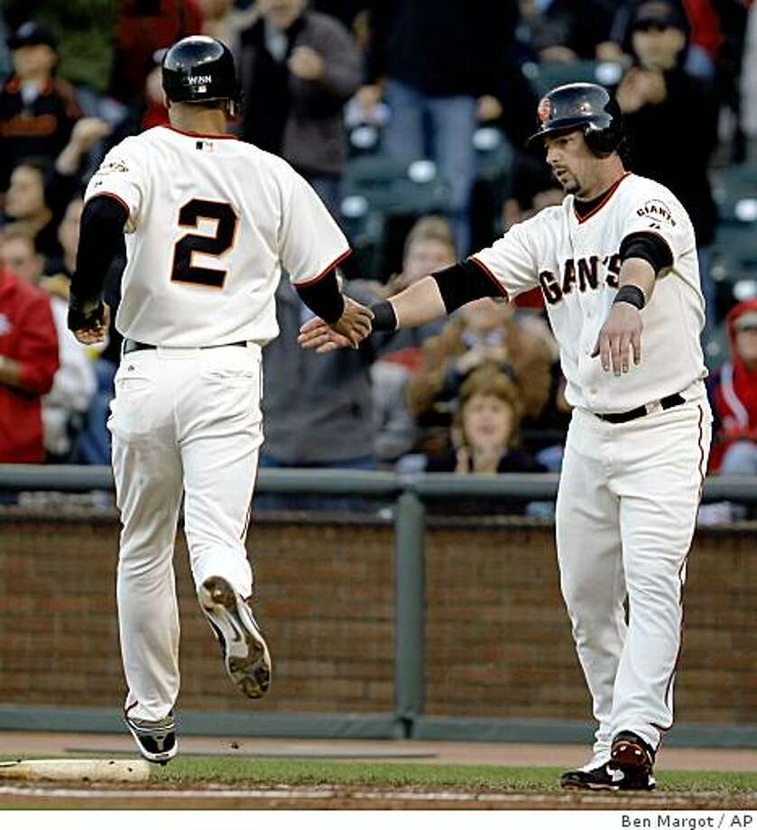 San Francisco Giants' Randy Winn and Aaron Rowand celebrate scoring against the St. Louis Cardinals during the first inning Friday in San Francisco. Photo: Ben Margot, AP