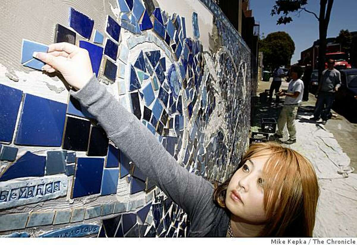 Lila Zhu, 17, a student at Ida B. Wells Highschool, helps put the finishing touches on a mural that was realized by Bay Area muralist, Josef Norris on Friday May 15, 2009 in San Francisco, Calif. The mural, which is on Fell Street is being created to honor prominant female heroes, both in their personal lives and in history, in honor of Women's History month.