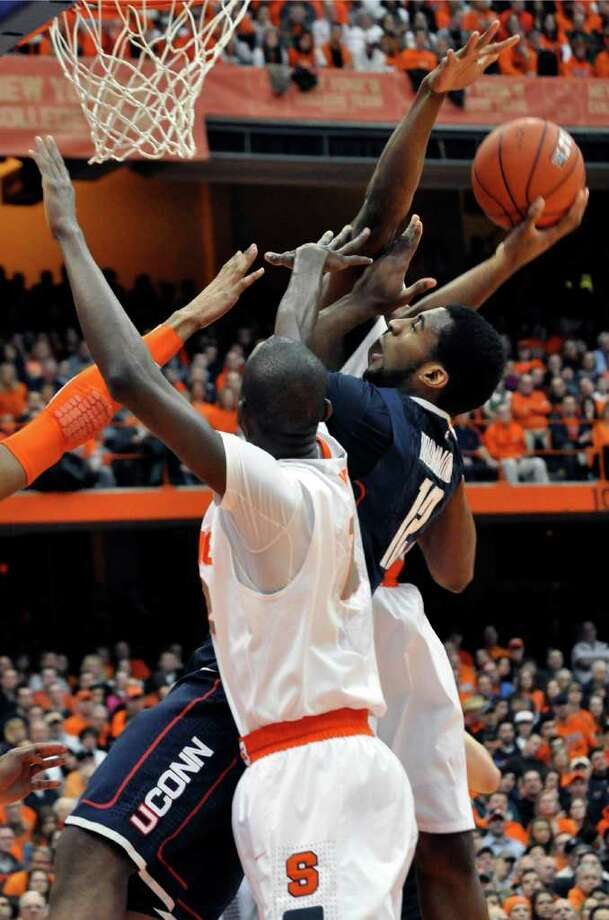 Connecticut's Andre Drummond tries to score between Syracuse defenders during the first half of an NCAA college basketball game in Syracuse, N.Y., Saturday, Feb. 11, 2012. (AP Photo/KevinRivoli) Photo: Kevin Rivoli, Kevin Rivoli/Associated Press / FR60349 AP