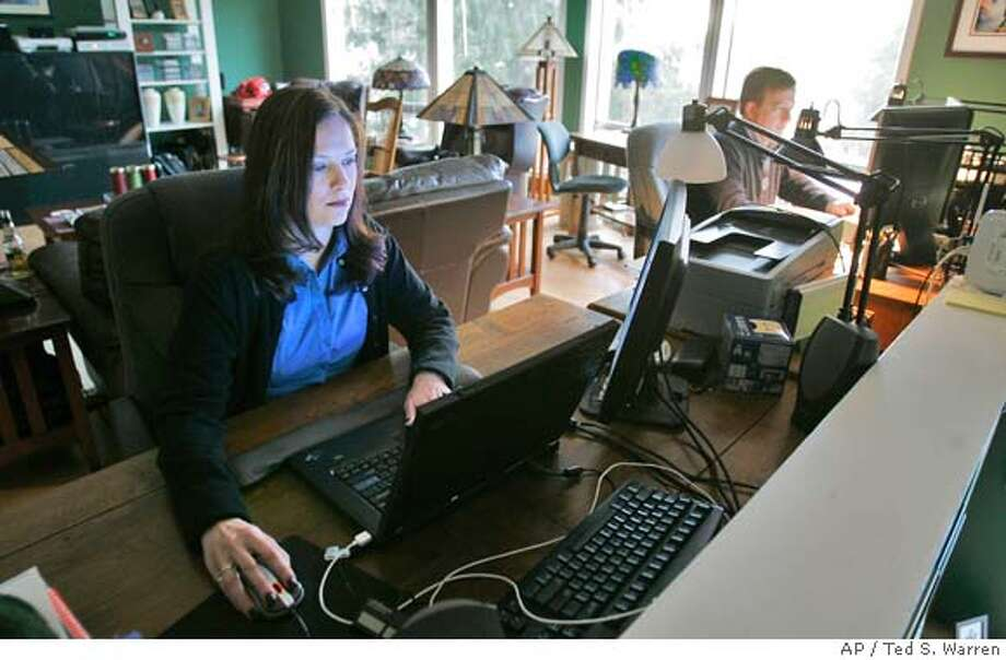 ** ADVANCE FOR TUESDAY, JAN. 22 ** Kate Herrick, left, looks through job openings posted online, while her husband Scot Herrick, right, works on his blog Wednesday, Jan. 16, 2008, at their home in Bellevue, Wash. Both were laid off from Washington Mutual Inc. late last year. (AP Photo/Ted S. Warren) Photo: Ted S. Warren