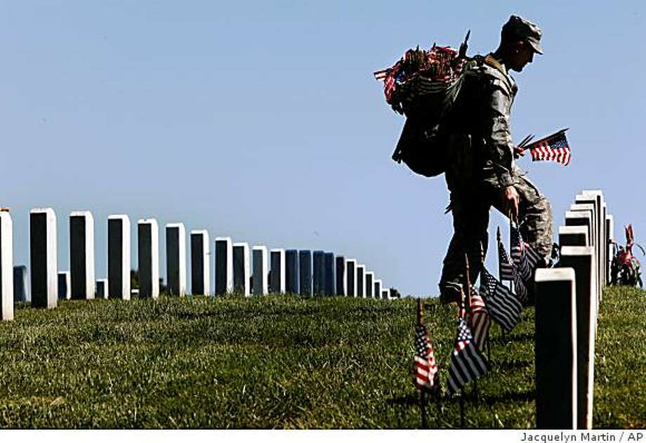 U.S. Army Pvt. Zach Lawson, 22, of Portland, Ore., places American flags on graves at Arlington National Cemetery for Memorial Day, in Arlington, Va. Thursday, May 21, 2009. (AP Photo/Jacquelyn Martin) Photo: Jacquelyn Martin, AP