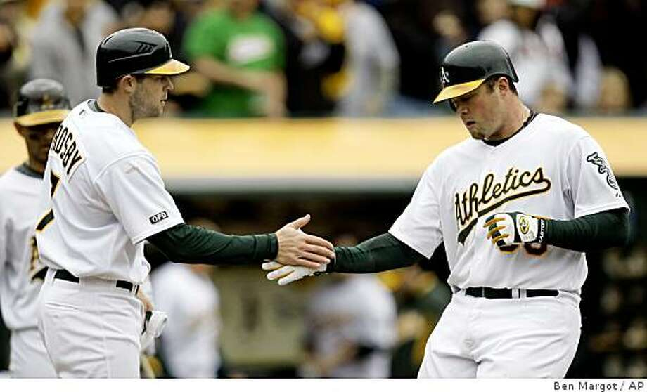 Oakland Athletics' Bobby Crosby, left, congratulates Landon Powell after Powell hit a two-run home run off Arizona Diamondbacks' Jon Garland in the sixth inning of a baseball game Sunday, May 24, 2009, in Oakland, Calif. (AP Photo/Ben Margot) Photo: Ben Margot, AP