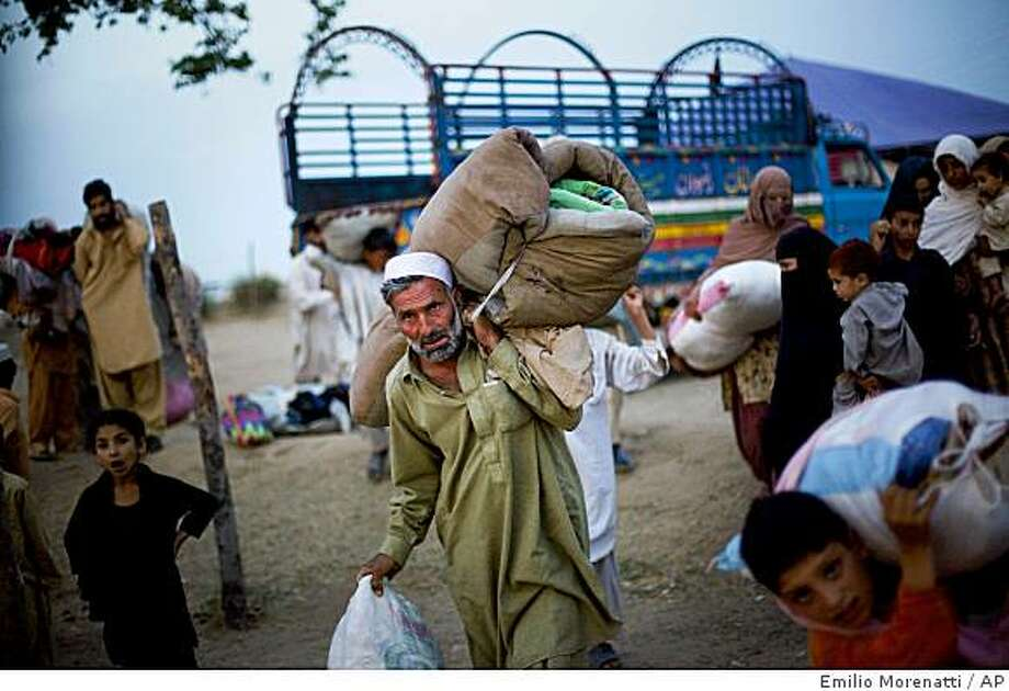 A Pakistani displaced man from Swat valley carries his belonging as he arrives with his family at Chota Lahore Refugee Camp in Swabi, Pakistan, Sunday, May 24, 2009. Hundreds of thousands of Pakistanis have fled fighting between the army and Taliban militants in a northwestern valley, raising the risk that public support could turn against an offensive Washington sees as a must-win battle. (AP Photo/Emilio Morenatti) Photo: Emilio Morenatti, AP