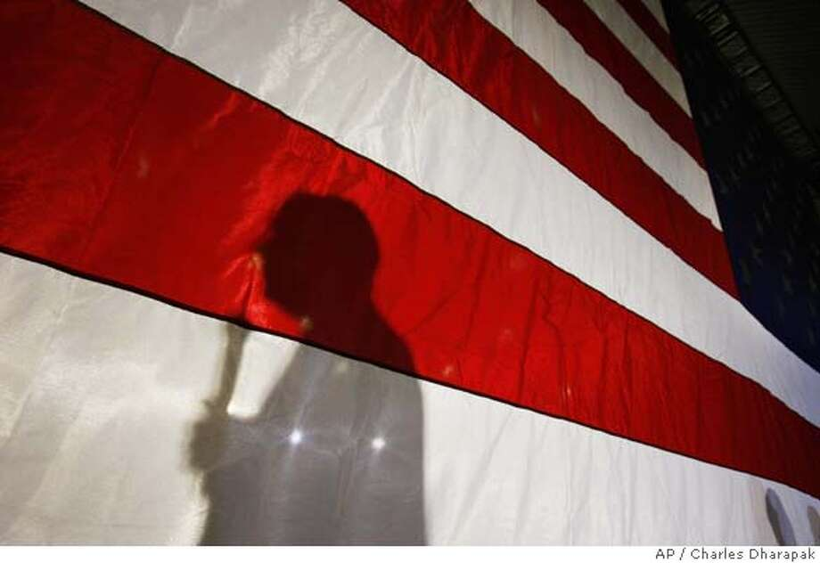 Republican presidential hopeful Sen. John McCain, R-Ariz., is silhouetted on a flag as he speaks at a campaign rally at Pensacola Junior College in Pensacola, Fla., Tuesday, Jan. 22, 2008. (AP Photo/Charles Dharapak) Photo: Charles Dharapak
