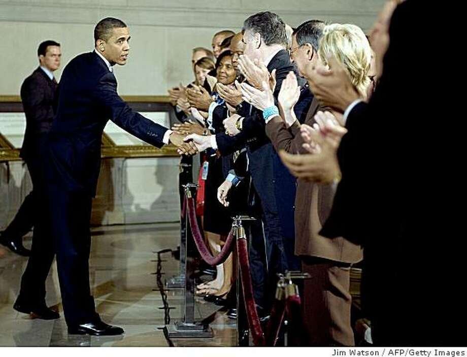 """US US President Barack Obama (C) shakes hands after delivering a major speech on national security at the US National Archives in Washington, DC, May 21, 2009. Obama Thursday vowed not to back down on closing Guantanamo Bay despite raging controversy, branding the camp a """"mess"""" and decrying Bush-era anti-terror tactics as based on fear. In a major speech designed to grab back control of the debate over national security policies, Obama also raised the prospect of holding the most dangerous Al-Qaeda detainees indefinitely in US """"super-max"""" jails.    TOPSHOTS/AFP PHOTO/Jim WATSON (Photo credit should read JIM WATSON/AFP/Getty Images) Photo: Jim Watson, AFP/Getty Images"""