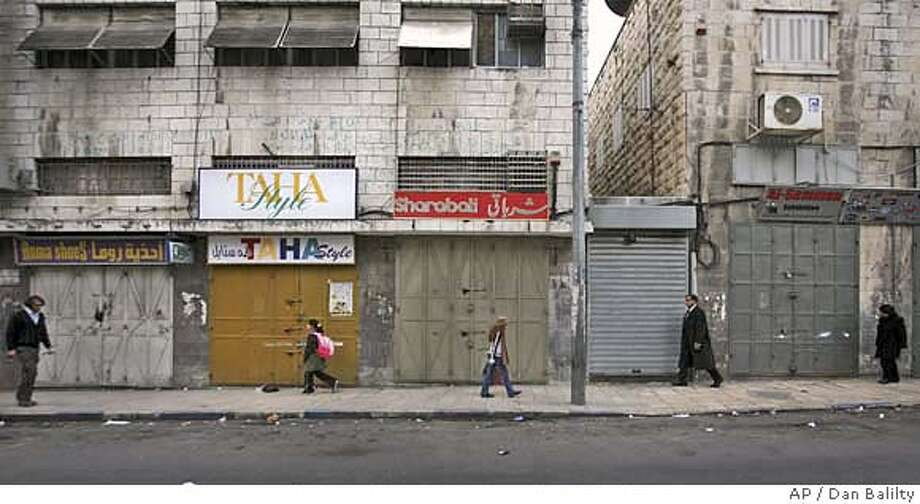 Palestinians are seen walking past closed shops in Salah Ad Din street, east Jerusalem, Monday, Jan. 21, 2008. On east Jerusalem's main Arab commercial street shops were shuttered and streets mostly deserted after traders observed a call for a one-day strike to protest against Israel's actions in Gaza. (AP Photo/Dan Balilty) Photo: DAN BALILTY