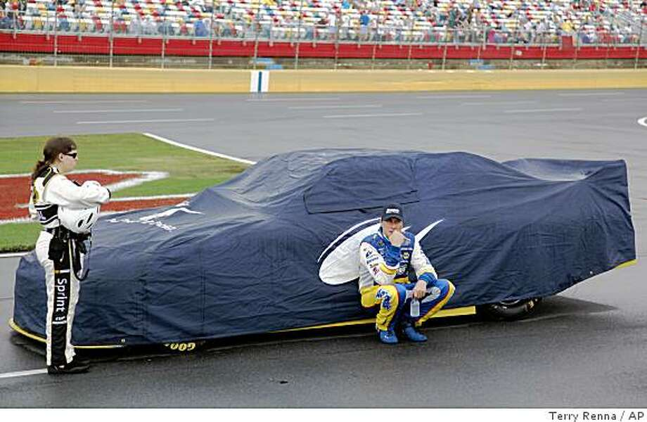 ** CORRECTS PHOTOGRAPHER'S NAME ** David Reutimann sits by his car during a rain delay in the NASCAR Coca-Cola 600 auto race at Lowe's Motor Speedway in Concord, N.C., Monday, May 25, 2009. (AP Photo/Terry Renna) Photo: Terry Renna, AP