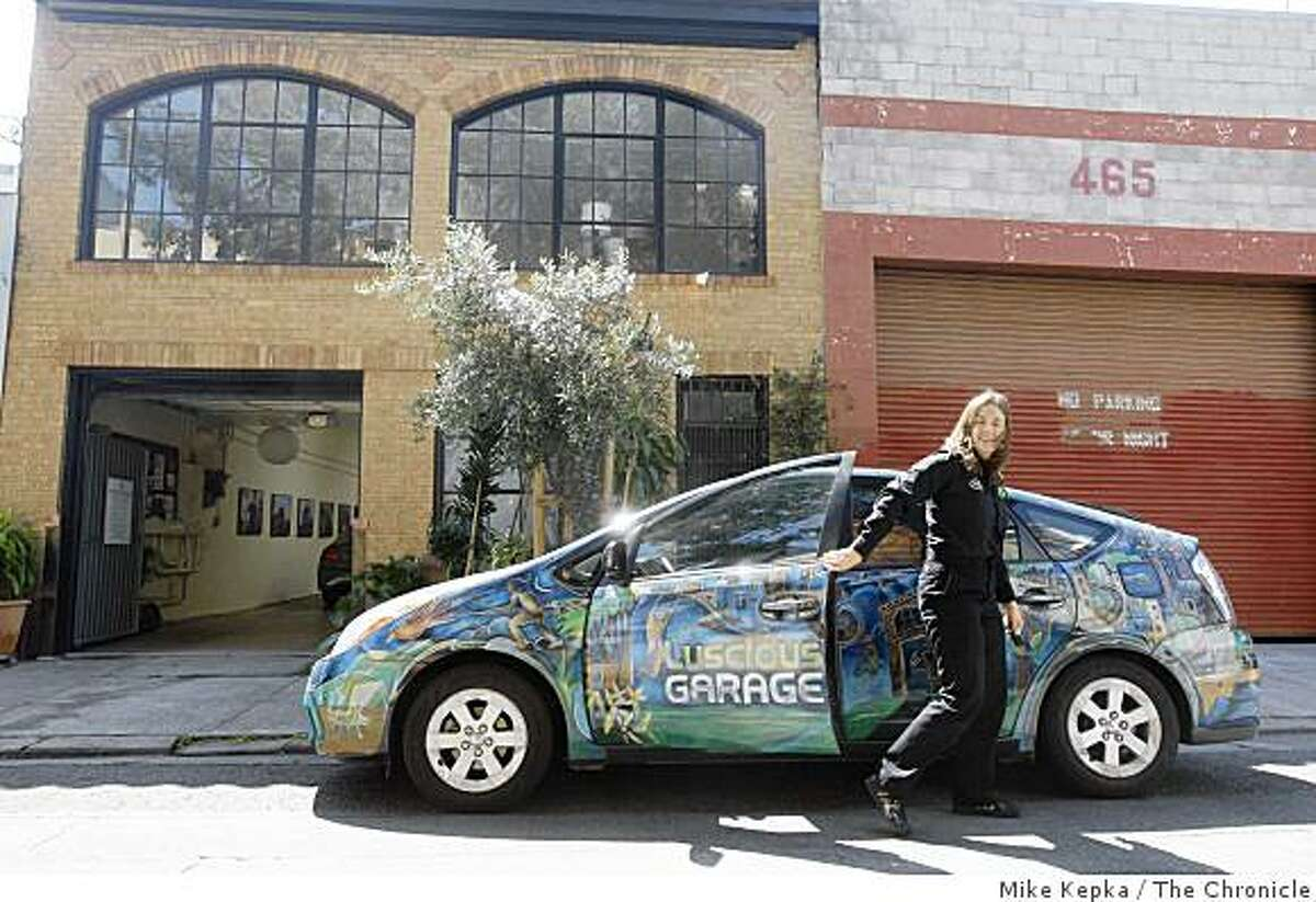 Carolyn Coquillette, owner and lead technition Luscious Garage, a SOMA auto repair garage that was the first in the nation to fully specialize on servicing hybrid electric-gas powered vehicles like the Prius when it opened less than two years ago, pulls into work in her customized Prius on Monday May 19, 2009 in San Francisco, Calif.