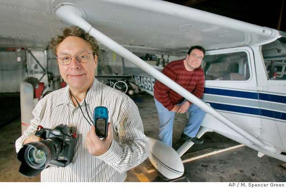 Aerial photographer Alan Goldstein, left, poses with a camera and a GPS mapping device next to the plane he uses at the DuPage Airport in West Chicago, Ill., Monday, Jan. 14, 2008. Pilot William Hamrick is seen at right. (AP Photo/M. Spencer Green) Photo: M. Spencer Green