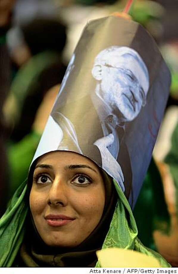 A supporter of Iranian presidential candidate Mir Hossein Mousavi (picture) attends a campaign rally in Tehran on May 23, 2009. Iran's former reformist president Mohammad Khatami openly threw his weight behind ex-premier Mousavi, who is contesting the June 12 presidential election. Khatami addressed the rally attended by a cheering crowd of men and women, many dressed in Mousavi's trademark colour green or wearing green scarves or wristbands. TOPSHOTS/AFP PHOTO/ATTA KENARE (Photo credit should read ATTA KENARE/AFP/Getty Images) Photo: Atta Kenare, AFP/Getty Images