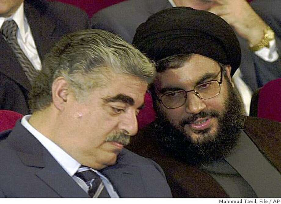FILE-In this May 25, 2001 file photo, former Lebanese Prime Minister Rafik Hariri, left, talks with Hezbollah leader Sheik Hassan Nasrallah, right, during an official ceremony to mark the first anniversary of the Israeli withdrawal from south Lebanon, in Beirut, Lebanon. Lebanon's militant Hezbollah group denied on Sunday May 24, 2009, a report by a German magazine linking it to the 2005 assassination of former Lebanese Prime Minister Rafik Hariri, saying it was an attempt to tarnish its image ahead of parliamentary elections.(AP Photo/Mahmoud Tawil, File) Photo: Mahmoud Tawil, File, AP