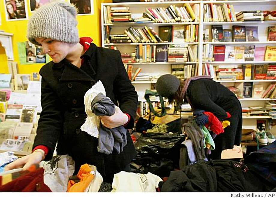 In this Feb. 22, 2009 photo, Frances Wood, left, and Sarah Hanks shop for free used clothing at a clothing swap sponsored by Brooklyn Clothing Exchange, in New York. Friends have been trading among themselves as long as parents have been handing down outgrown baby clothes. Now, with some help from the Internet, swaps among strangers are cropping up in bars, schools, garages and churches across the United States.  (AP Photo/Kathy Willens) Photo: Kathy Willens, AP