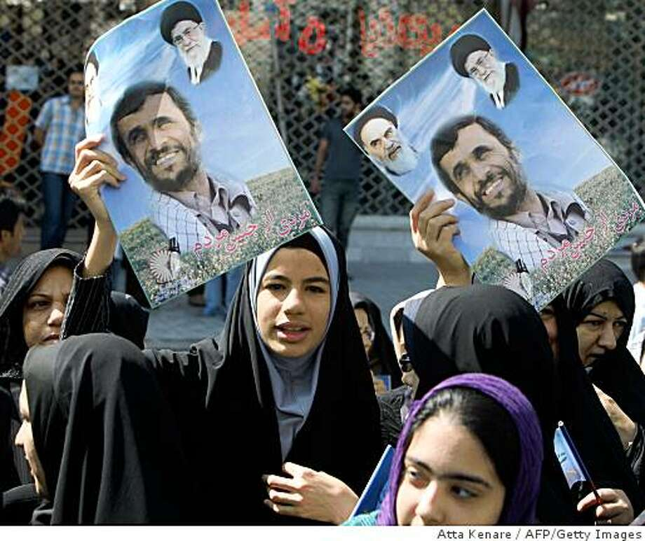 Iranian women hold up portraits of President Mahmoud Ahmadinejad (C) as they listen to his speech in Semnan, 210 kms west of Tehran, on May 20, 2009. Ahmadinejad said in a speech during his visit to the northern town that Iran has test-fired a new medium-range surface to surface missile, named Sejil-2. Two other portraits on top of the posters show Iran's supreme leader Ayatollah Ali Khamenei (R) and his predecessor, the founder of the Islamic republic Ayatollah Ruhollah Khomeini. AFP PHOTO/ATTA KENARE (Photo credit should read ATTA KENARE/AFP/Getty Images) Photo: Atta Kenare, AFP/Getty Images