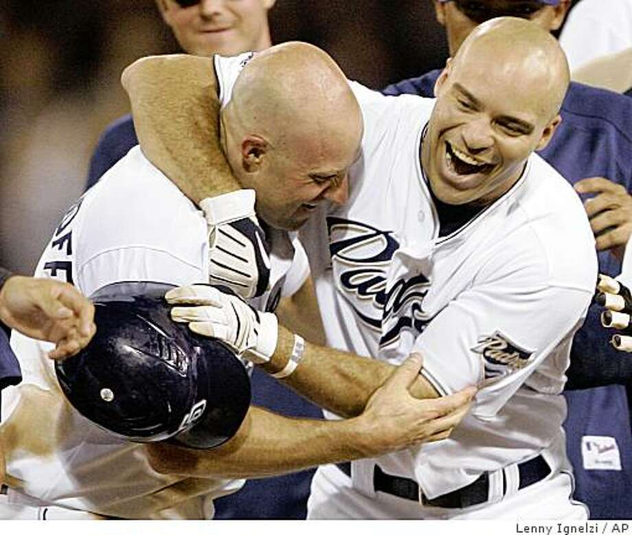San Diego Padres' Scott Hairston, right, celebrates with teammate Kevin Kouzmanoff, after Hairston's  game winning  single in the bottom of the ninth inning gave the Padres their sixth straight victory with a 3-2 win over the San Francisco Giants in their baseball game on  Thursday, May 21, 2009 in San Diego.  (AP Photo/Lenny Ignelzi) Photo: Lenny Ignelzi, AP