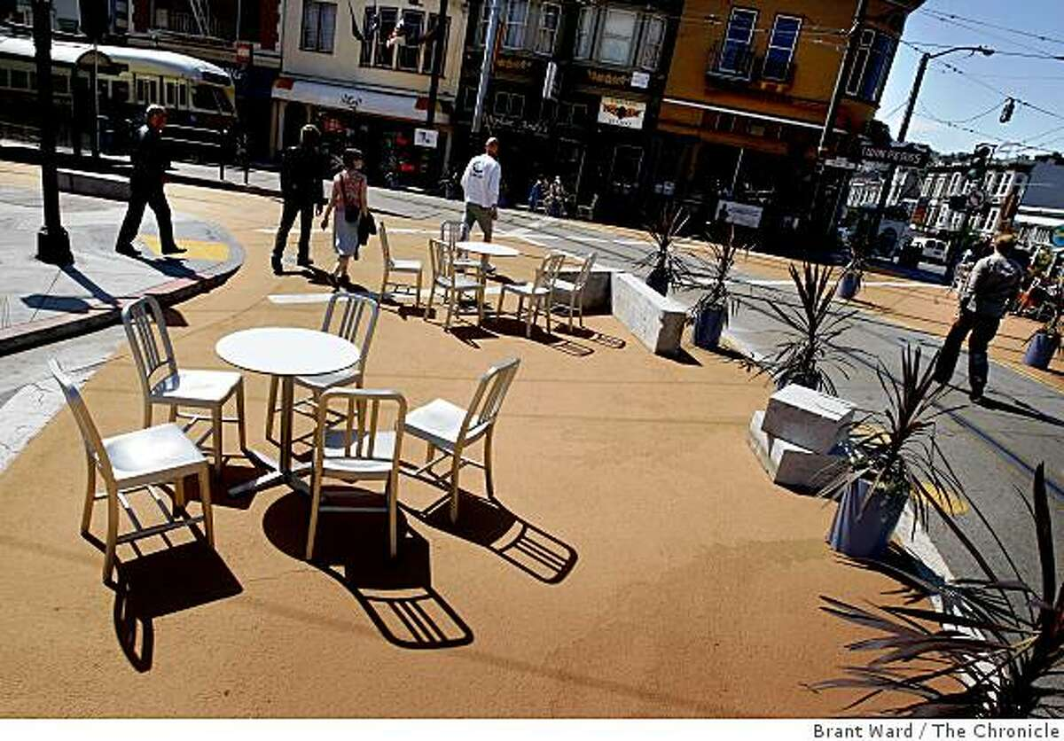 Tables and chairs cast shadows in the morning light as pedestrians make their way through the plaza. A temporary public plaza at the end of the streetcar line at 17th Street and Castro Streets in San Francisco, CA creates a place where people can linger and watch the world go by.